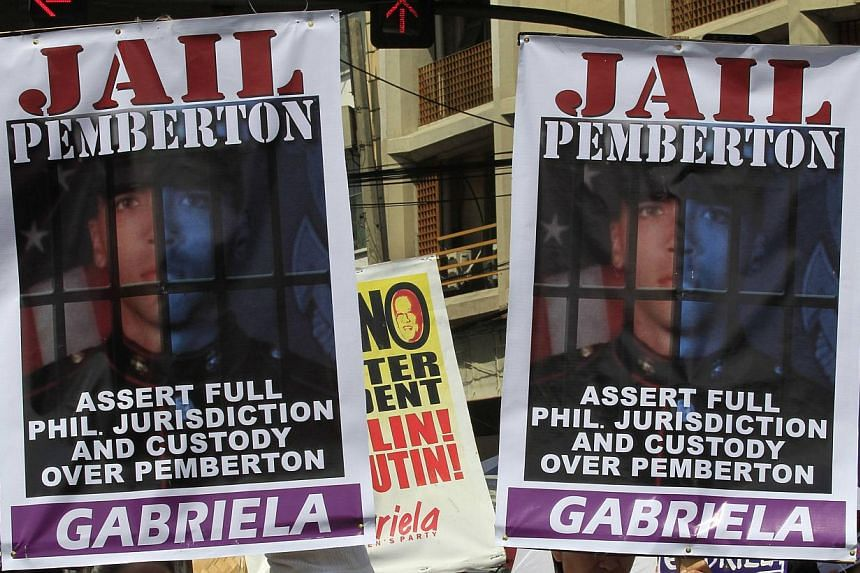 Activists display placards of US Marine Private First Class Joseph Scott Pemberton during a protest outside the presidential palace in Manila on Oct 28, 2014. -- PHOTO: REUTERS