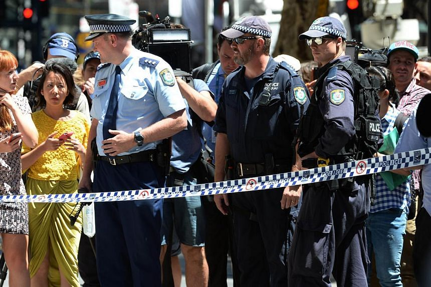Police talk to the public near a cafe in the central business district of Sydney on Dec 15, 2014. -- PHOTO: AFP