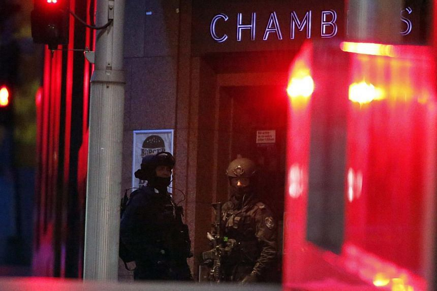 Heavily armed policemen stand guard outside the building containing the Lindt cafe, where hostages are being held, at Martin Place in central Sydney on Dec 15, 2014. -- PHOTO: REUTERS