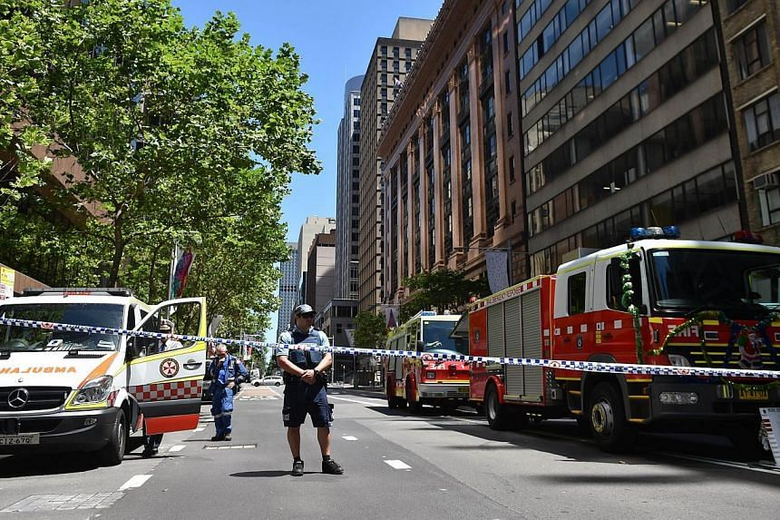 A policeman guards a road leading to a cafe in the central business district of Sydney on Dec 15, 2014. -- PHOTO: AFP