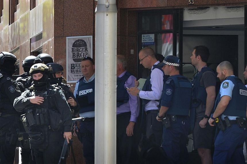Armed police are seen outside a cafe in the central business district of Sydney on Dec 15, 2014. Hostages were being held inside a cafe in central Sydney with an Islamic flag displayed against a window, according to witnesses and reports, while polic