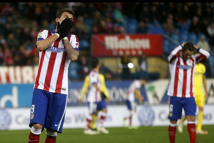 Atletico Madrid's Mario Mandzukic (left) and Koke react during their Spanish first division soccer match against Villareal at Vicente Calderon stadium in Madrid on Sunday. -- PHOTO: REUTERS