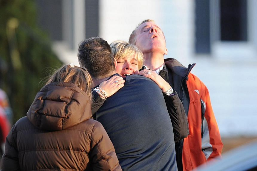 Unidentified people embrace December 14, 2012, at the scene from the aftermath of a school shooting at an elementary school in Newtown, Connecticut that brought police swarming into the leafy neighborhood, while other area schools were put under lock