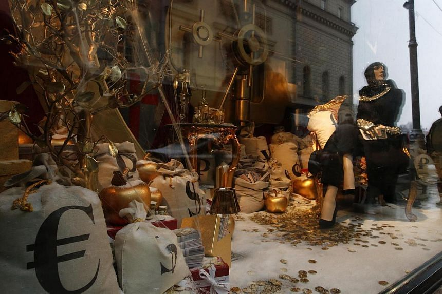 Passers-by being reflected in a Moscow shop window displaying bags labelled with currency signs for the euro, US dollar and rouble on Dec 10, 2014. -- PHOTO: REUTERS
