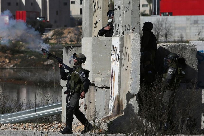 An Israeli soldier fires a smoke grenade towards students from Birzeit University (background) during clashes at the entrance of the Israeli Ofer military prison, near the West Bank village of Betunia, on Dec 13, 2014, following a march organized aga