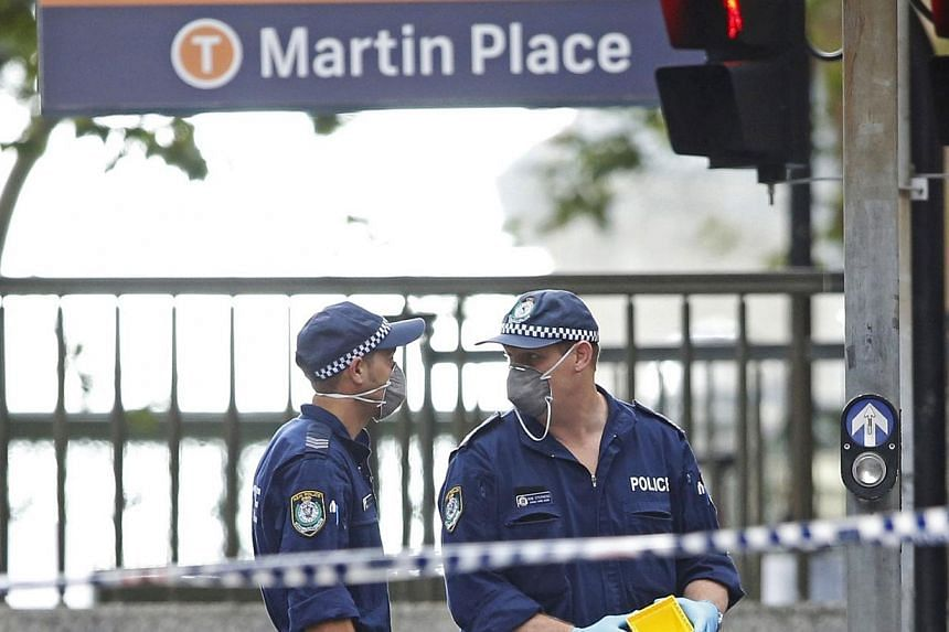 New South Wales police officers wear protective masks as they place marker cones over potential evidence in their investigation into the Sydney cafe siege, on Tuesday, Dec 16, 2014. The Asian Football Confederation said on Tuesday that it had as