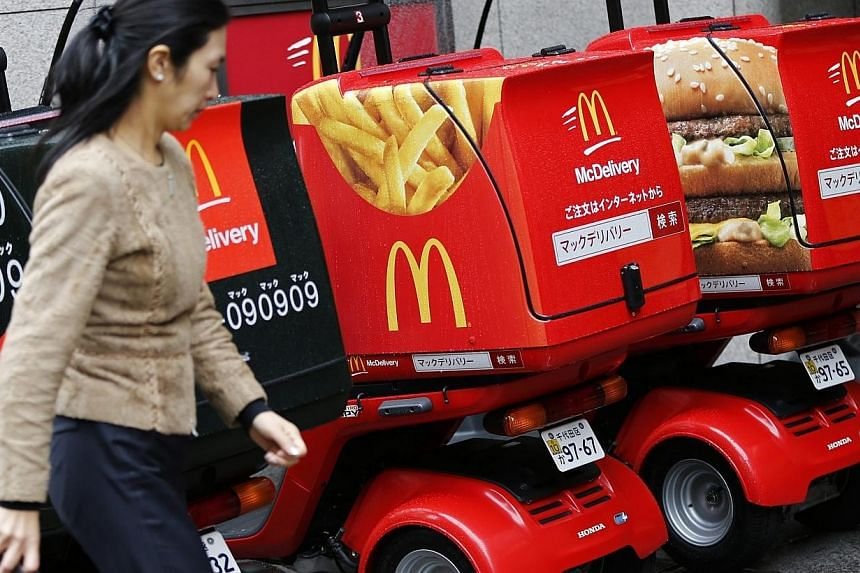 A woman walks past delivery scooters decorated with pictures of McDonald's food, including a packet of fries and a Big Mac burger, outside a McDonald's store in Tokyo on Dec 16, 2014. -- PHOTO: REUTERS