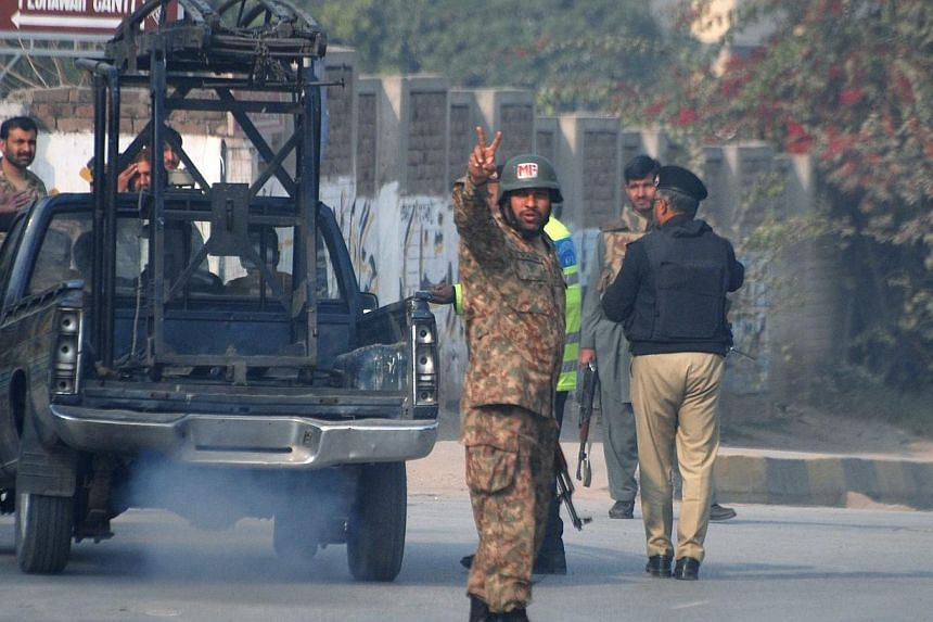 A soldier gestures on a road leading to the Army Public School that is under attack by Taleban gunmen in Peshawar, on Dec 16, 2014. -- PHOTO: REUTERS