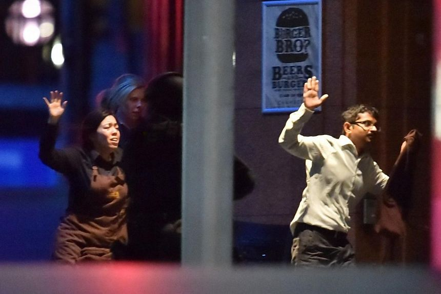 Hostages run out of a cafe in the central business district of Sydney on Dec 16, 2014.Ms Harriette Denny (left) was able to escape just minutes before the siege ended in gunfire on Tuesday. -- PHOTO: AFP