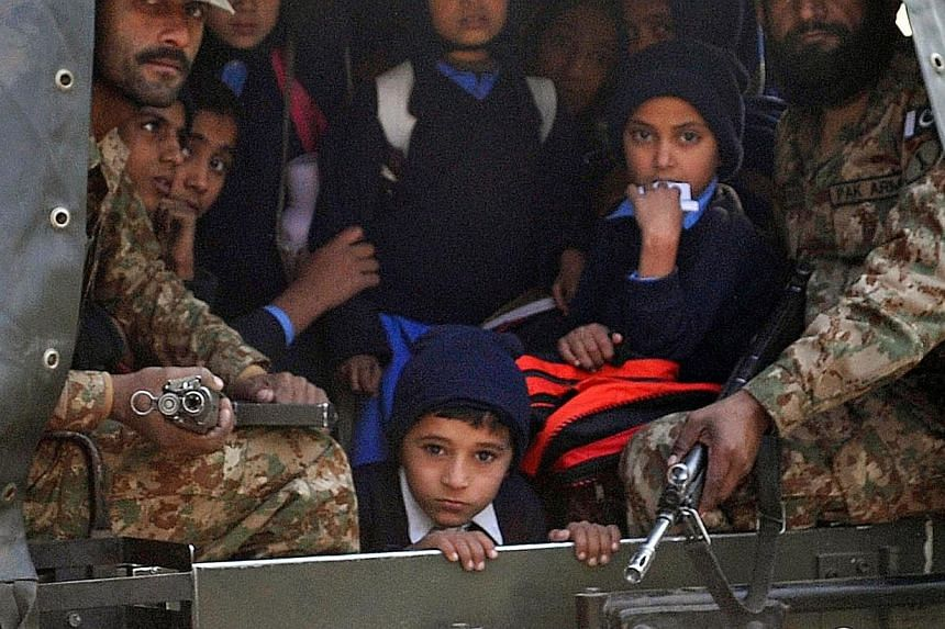 Pakistani soldiers transport rescued school children from the site of an attack by Taleban gunmen on a school in Peshawar on Dec 16, 2014. -- PHOTO: AFP