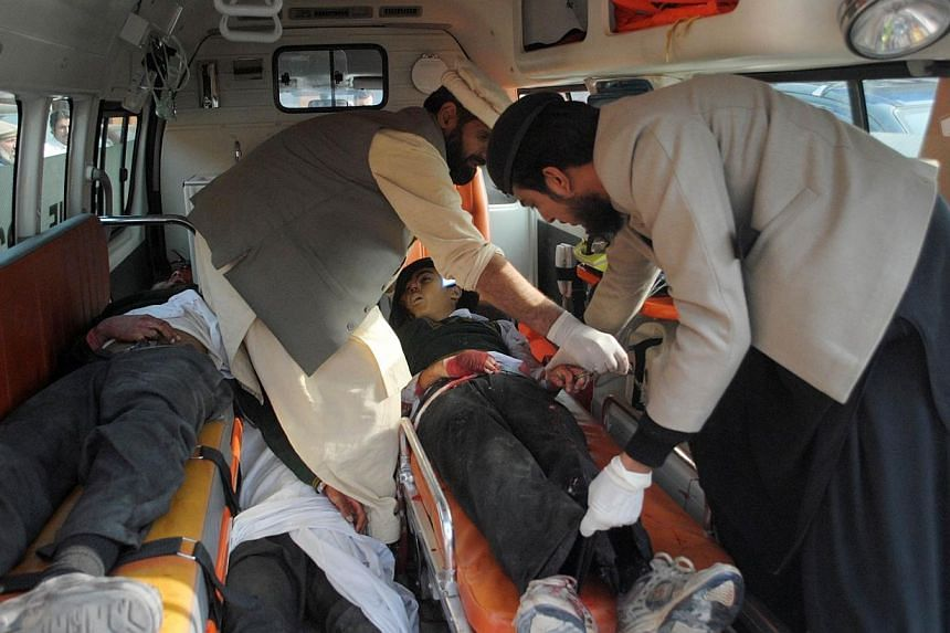 Men move bodies of students, who were killed during an attack by Taleban gunmen on the Army Public School, in an ambulance outside a hospital in Peshawar, on Dec 16, 2014. -- PHOTO: REUTERS