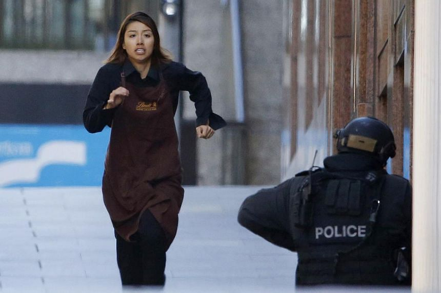 Ms Elly Chen, one of the hostages who survived the 16-hour siege, runs towards a police officer on Dec 15, 2014. -- PHOTO: AFP