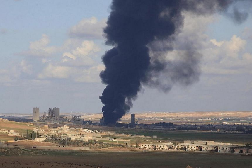 Smoke rises from burning warehouses, reportedly belonging to rebel fighters, in al-Maslamiyeh village,after Syria's army regained control of the area in north of Aleppo on Dec 15, 2014.An Indonesian man suspected of facilitating trips by