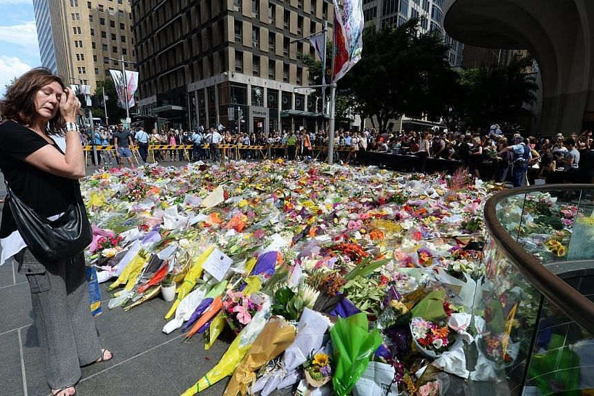 A visitor looks at a makeshift memorial near the scene of a fatal siege in the heart of Sydney's financial district on Dec 16, 2014.-- PHOTO: AFP