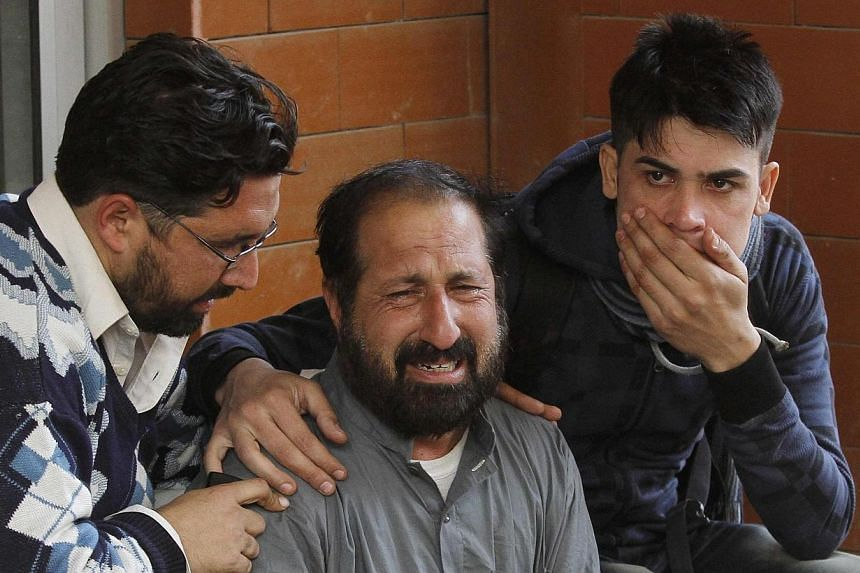 Relatives of a student, who was injured during an attack by Taleban gunmen on the Army Public School, comfort each other outside Lady Reading Hospital in Peshawar, on December 16, 2014.-- PHOTO: AFP