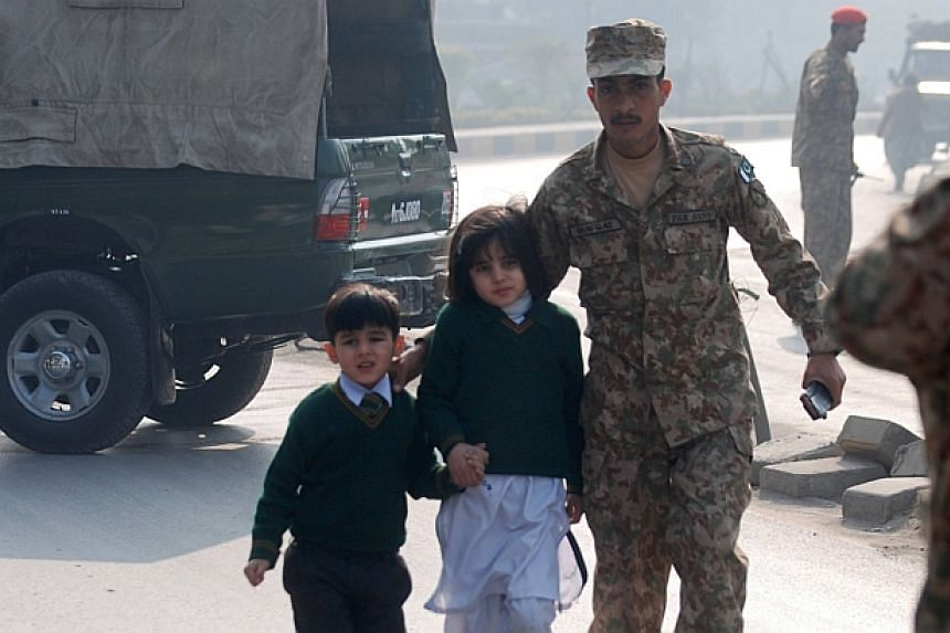 A soldier escorts schoolchildren after they were rescued from from the Army Public School that is under attack by Taleban gunmen in Peshawar on Dec 16, 2014. -- PHOTO: REUTERS