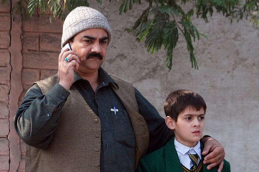 A man talks on a phone, with his arm around a student, outside a military run school that is under attack by Taleban gunmen in Peshawar on Dec 16, 2014. -- PHOTO: REUTERS