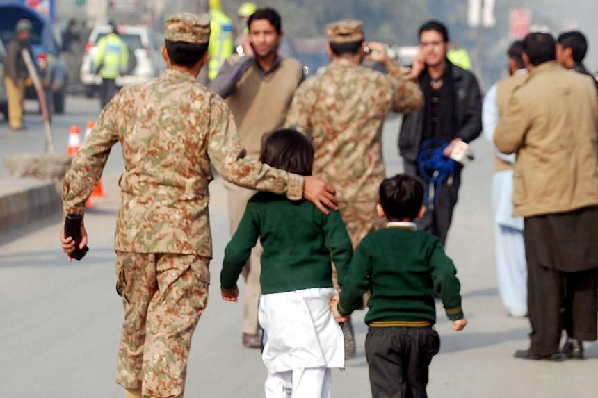 A soldier escorts schoolchildren after they were rescued from the Army Public School that is under attack by Taleban gunmen in Peshawar on Dec 16, 2014. -- PHOTO: REUTERS