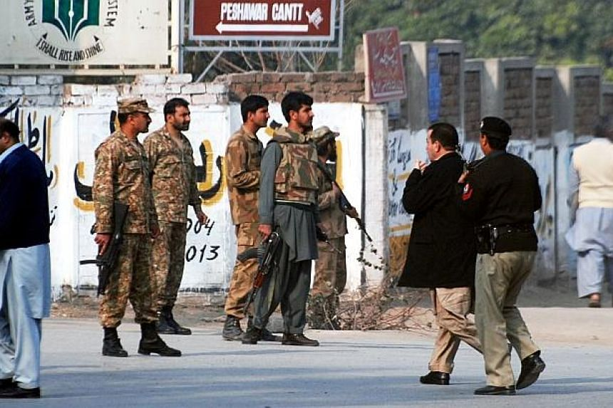Pakistani security forces takes up a positions on a road leading to the Army Public School that is under attack by Taleban gunmen in Peshawar on Dec 16, 2014. -- PHOTO: REUTERS
