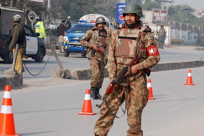 Pakistani security forces takes up positions on a road leading to the Army Public School that is under attack by Taleban gunmen in Peshawar on Dec 16, 2014. -- PHOTO: REUTERS