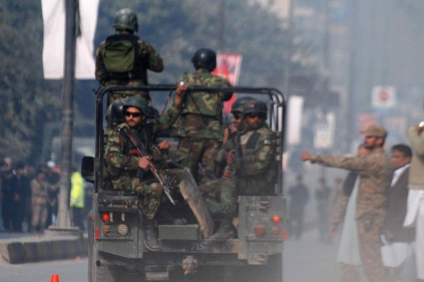 Pakistani security forces drive on a road leading to the Army Public School that is under attack by Taleban gunmen in Peshawar on Dec 16, 2014. -- PHOTO: REUTERS