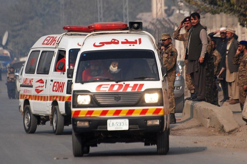 Ambulances drive away from a military-run school that is under attack by Taleban gunmen in Peshawar on Dec 16, 2014. -- PHOTO: REUTERS
