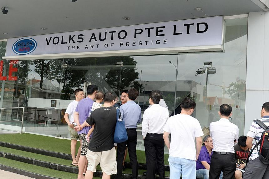 More than 20 people gathered outside Volks Auto, a car dealership in MacPherson Road, on Monday, Dec 15, 2014.Car buyers demanding refunds turned up for the second day in a row on Tuesday, as a WhatsApp chat group of car buyers claiming they ha
