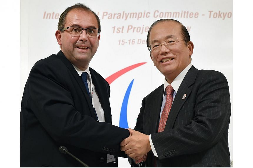 International Paralympic committee CEO Xavier Gonzalez (left) shakes hands with Tokyo Organising Committee of the Olympic and Paralympic Games CEO Toshiro Muto (right) in Tokyo on Dec 16, 2014.-- PHOTO: AFP