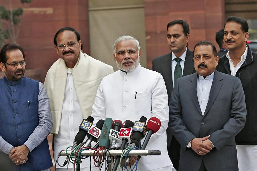 India's Prime Minister Narendra Modi (third left) speaks on the opening day of the winter session of the Indian Parliament, flanked by members of his Cabinet, in New Delhi on Nov 24, 2014. India's Parliament was thrown into disarray on Dec