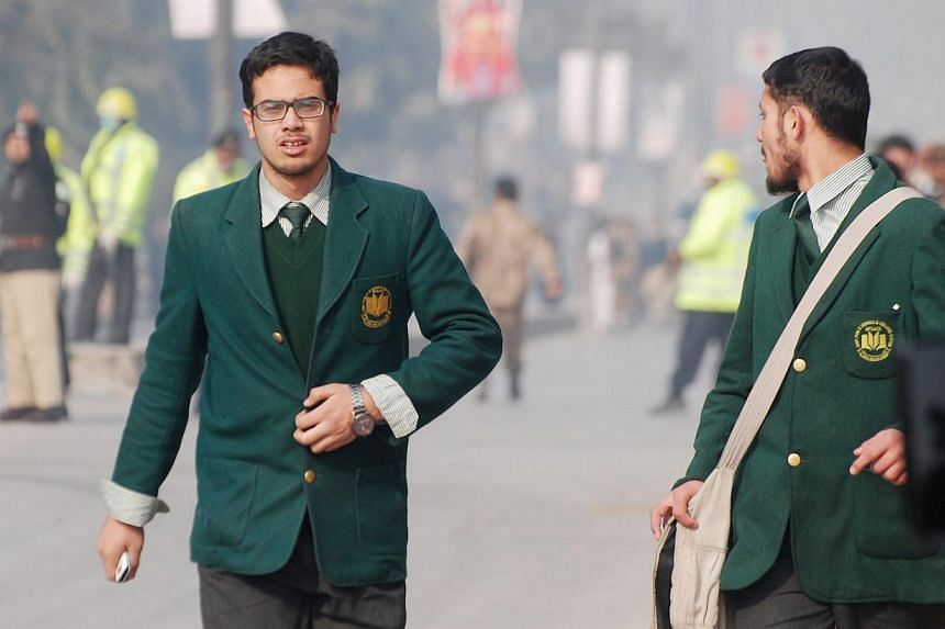 Students walk near the Army Public School that in under attack by Talban gunmen in Peshawar, on Dec 16, 2014. Militants in Pakistan said their attack on a school in Peshawar on Tuesday was vengeance for an army offensive on Taleban insurgents. -