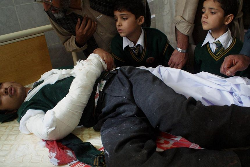 An injured Pakistani student lies on a bed at a hospital following an attack by Taleban gunmen on a school in Peshawar on Dec 16, 2014. -- PHOTO: AFP