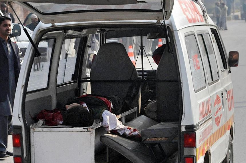 An ambulance transports a wounded student, whose fate is unknown, near the site of an attack by Taleban gunmen on a school in Peshawar on Dec 16, 2014. -- PHOTO: AFP
