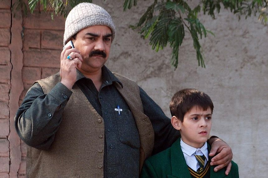 A man talks on a phone, with his arm around a student, outside a military run school that is under attack by Taleban gunmen in Peshawar, on Dec 16, 2014. -- PHOTO: REUTERS
