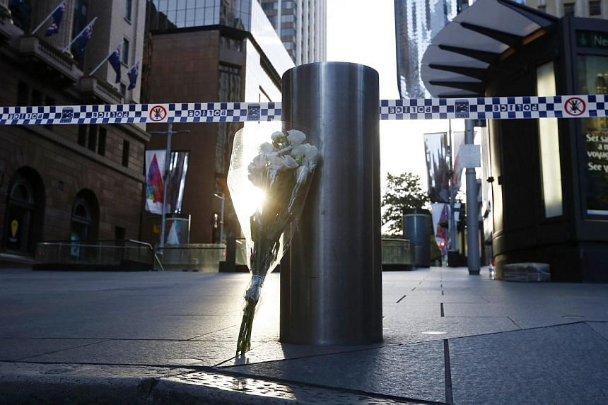A bouquet under a police tape near the cordoned-off scene at Martin Place after the siege ended early on Dec 16, 2014.-- PHOTO: REUTERS