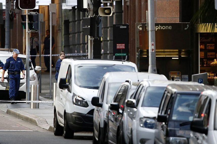 New South Wales police inspect the area near the scene of a siege in a cafe (right) in Sydney's Martin Place on Dec 16, 2014. -- PHOTO: REUTERS