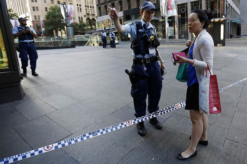 An office worker is stopped by a policewoman at a cordoned-off area near the site of a siege in a cafe at Sydney's Martin Place on Dec 16, 2014. -- PHOTO: REUTERS