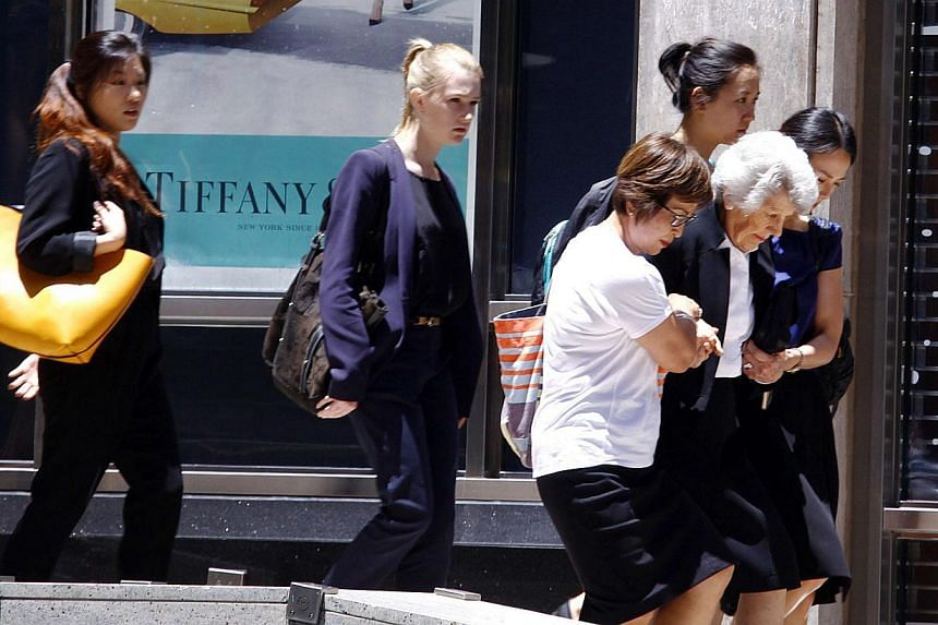 A woman is assisted as a group of people are evacuated by police from a building next to Lindt cafe in Martin Place in central Sydney on Dec 15, 2014. -- PHOTO: REUTERS