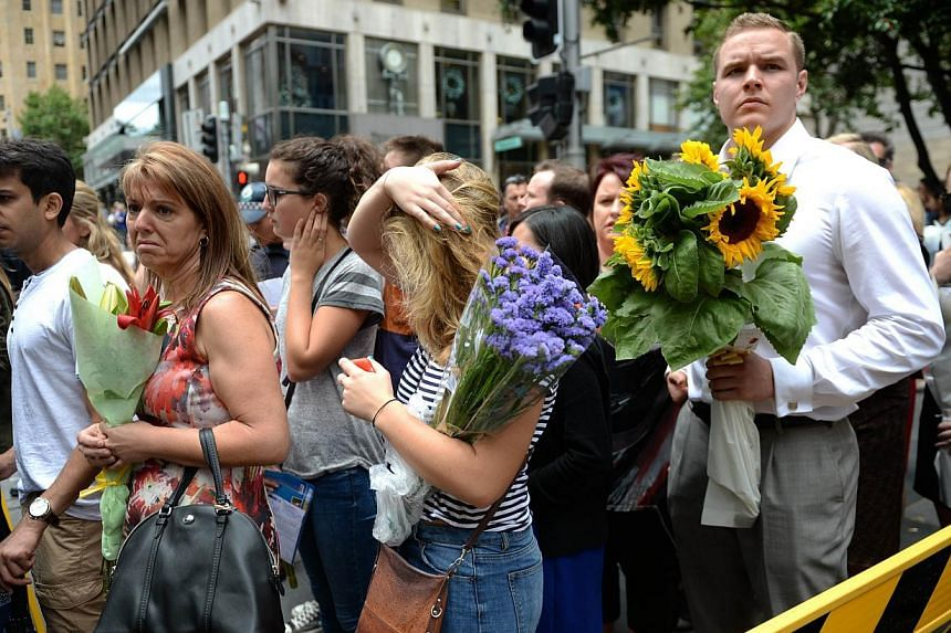 Visitors queue up to lay flowers at a makeshift memorial near the scene of a fatal siege in the heart of Sydney's financial district on Dec 16, 2014. -- PHOTO: AFP