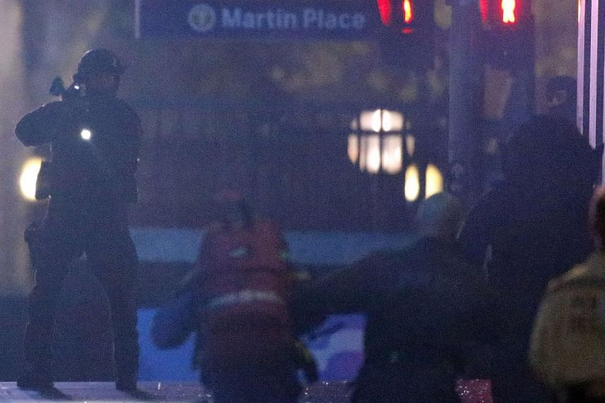 A heavily armed policeman holds his weapon as paramedics rush towards the Lindt cafe, where hostages are being held, at Martin Place in central Sydney on Dec 16, 2014. -- PHOTO: REUTERS