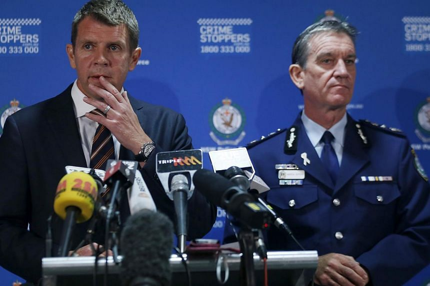 New South Wales Police Commissioner Andrew Scipione (right) and New South Wales Premiere Mike Baird conduct a press conference related to the siege at a Sydney cafe, hours after the siege ended on Dec 16, 2014. -- PHOTO: REUTERS