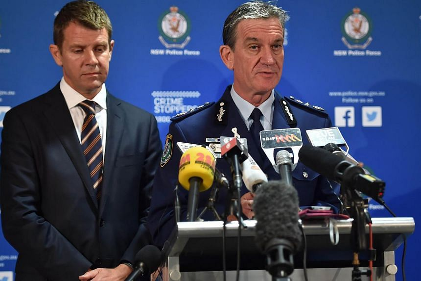 New South Wales Police Commissioner Andrew Scipione (right) speaks alongside New South Wales Premier Mike Baird (left) during a press conference about the siege in a cafe in the central business district of Sydney on Dec 16, 2014. -- PHOTO: AFP