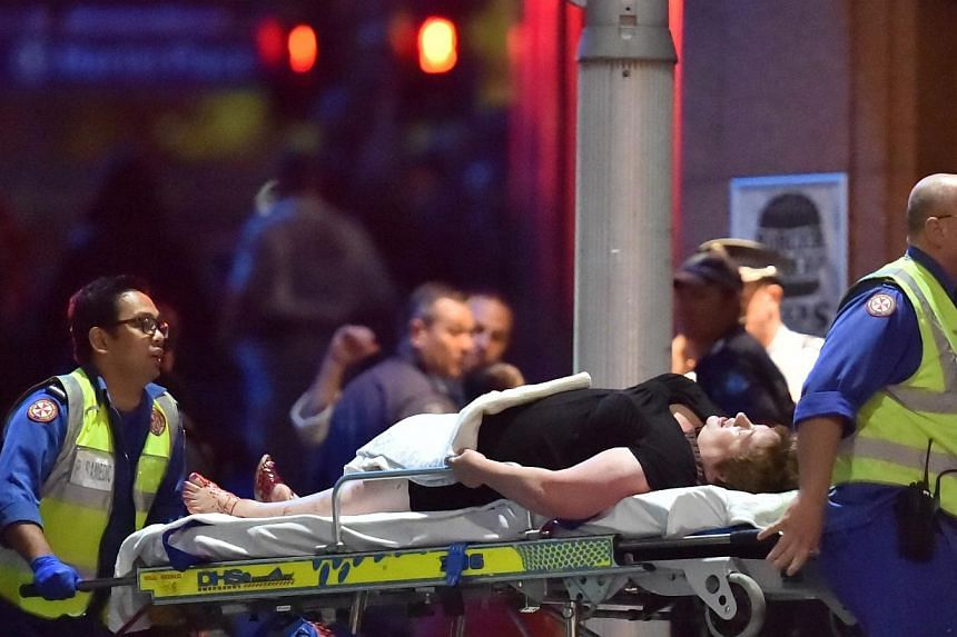 An injured hostage is carried out of a cafe in the central business district of Sydney on Dec 16, 2014. -- PHOTO: AFP