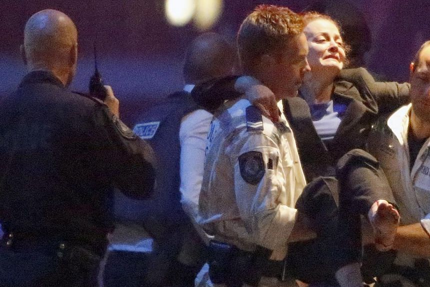 Police rescue personnel carry an injured woman from the Lindt cafe, where hostages are being held, at Martin Place in central Sydney on Dec 16, 2014. -- PHOTO: REUTERS