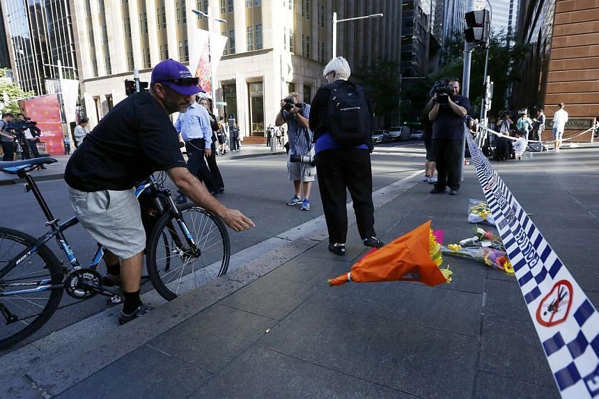 A man on a bicycle tosses a bouquet towards a police line restricting access to the site of a Sydney cafe siege after it ended on Dec 16, 2014. -- PHOTO: REUTERS