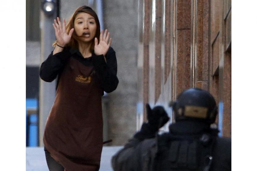 A hostage runs towards a police officer outside Lindt cafe, where other hostages are being held, in Martin Place in central on Sydney Dec 15, 2014. -- PHOTO: REUTERS