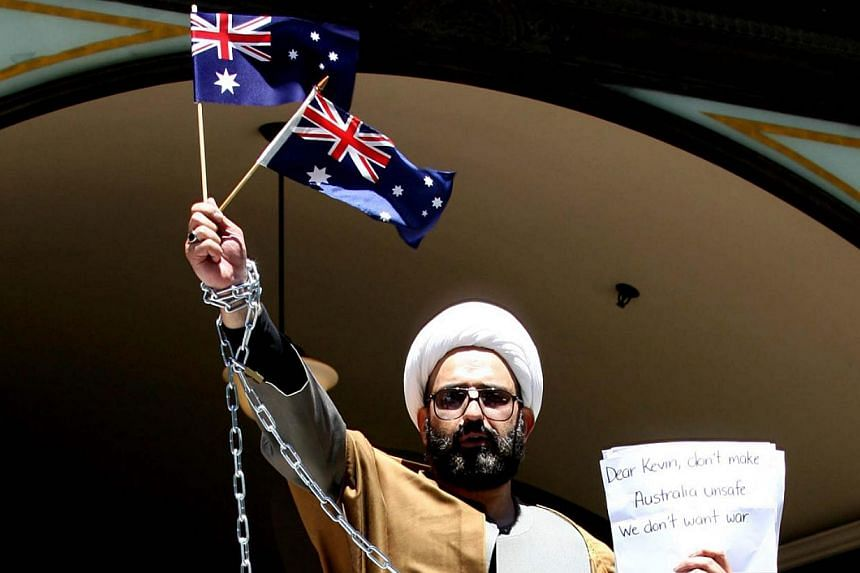 Iranian born Muslim cleric, Sheik Haron, who is named in court papers as Man Haron Monis, chained to a railing outside the Downing Centre Court in Sydney in an anti-war protest. -- PHOTO: CAMERON RICHARDSON/NEWSPIX/REX