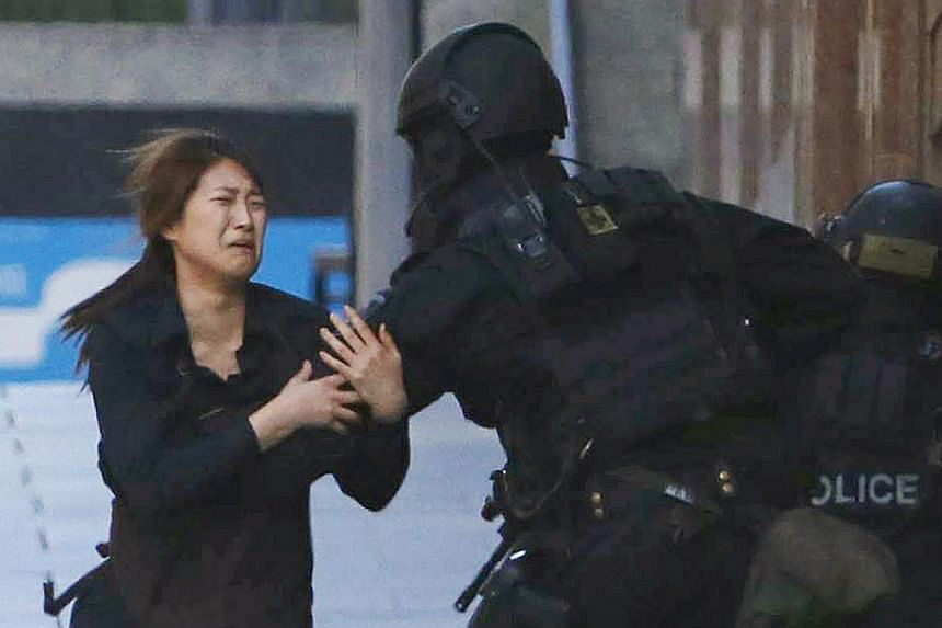 Student and barista Bae Ji Eun dashing into the arms of apolice officer outside Lindt cafe, where other hostages are being held, in Martin Place in central Sydney on Dec 15, 2014. -- PHOTO: REUTERS