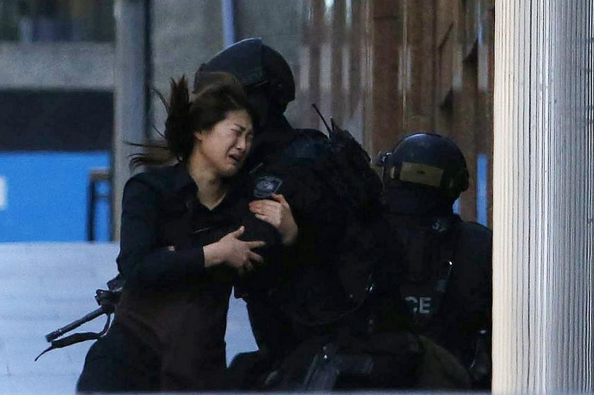 Student and barista Bae Ji Eun dashing into the arms of apolice officeroutside Lindt cafe, where other hostages are being held, in Martin Place in central Sydney on Dec 15, 2014. -- PHOTO: REUTERS