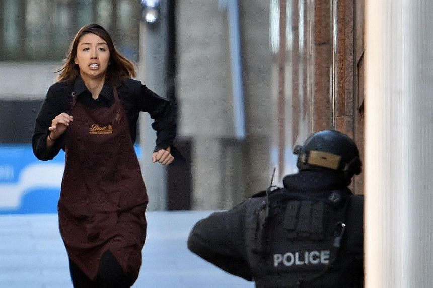 Ms Bae's fellow worker Elly Chen runs towards police from Sydney's Lindt cafe on Dec 15, 2014. -- PHOTO: AFP