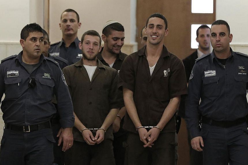 Three Israeli suspects, members of the right-wing Lehava organisation, are escorted by security to a hearing at the District Court in Jerusalem on Dec 15, 2014. -- PHOTO: AFP